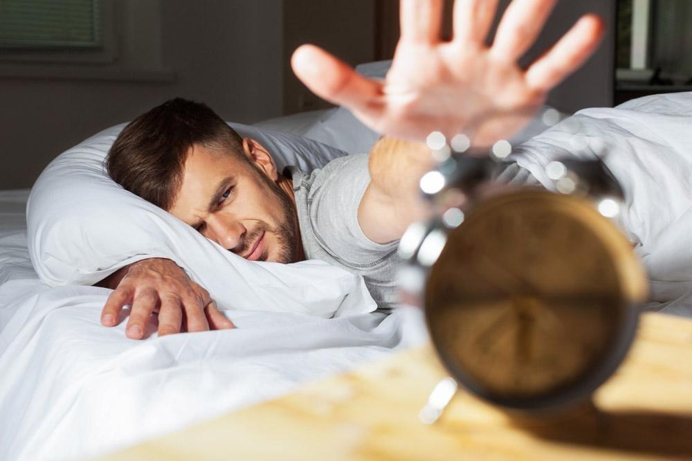 Man About Reach his Alarm Clock